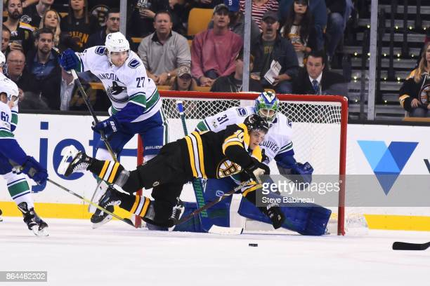 Anders Bjork of the Boston Bruins falls on the ice against Ben Hutton and Anders Nilsson of the Vancouver Canucks at the TD Garden on October 19 2017...