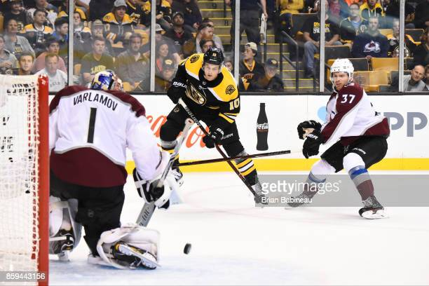 Anders Bjork of the Boston Bruins shoots the puck against Semyon Varlamov and JT Compher of the Colorado Avalanche at the TD Garden on October 9 2017...