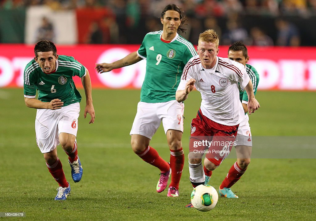 Anders Christiansen #8 of Denmark controls the ball past Hector Herrera #6 and Also Peralta #9 of Mexico during an international friendly match at University of Phoenix Stadium on January 30, 2013 in Glendale, Arizona. Mexico and Denmark ended in a 1-1 draw.