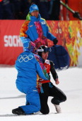 Anders Jacobsen of Norway is given assistance after his jump during the Men's Normal Hill Individual Ski Jumping training ahead of the Sochi 2014...