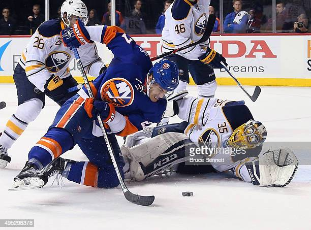 Anders Lee of the New York Islanders attempts to control the puck in front oif Linus Ullmark of the Buffalo Sabres during the second period at the...