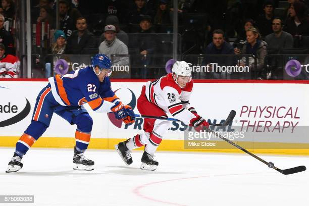 Anders Lee of the New York Islanders battles for the puck against Brett Pesce of the Carolina Hurricanes at Barclays Center on November 16 2017 in...