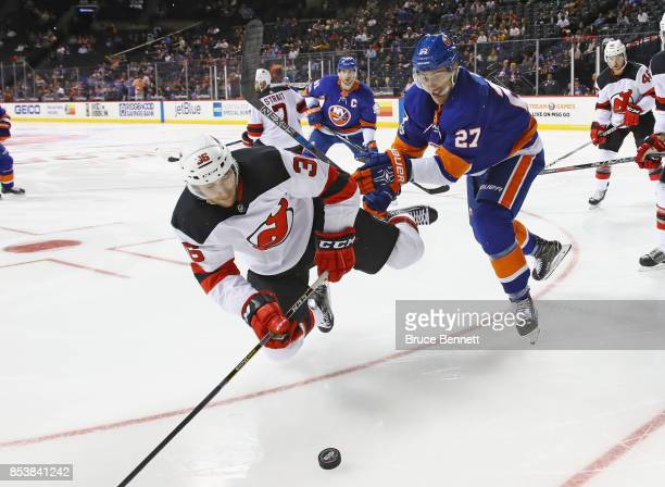 Anders Lee of the New York Islanders knocks Stefan Noesen of the New Jersey Devils off the puck in the second period during a preseason game at the...