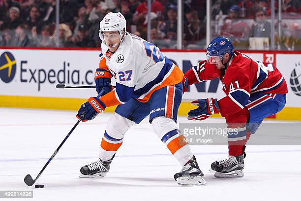 Anders Lee of the New York Islanders protects the puck from Paul Byron of the Montreal Canadiens in the NHL game at the Bell Centre on November 22...