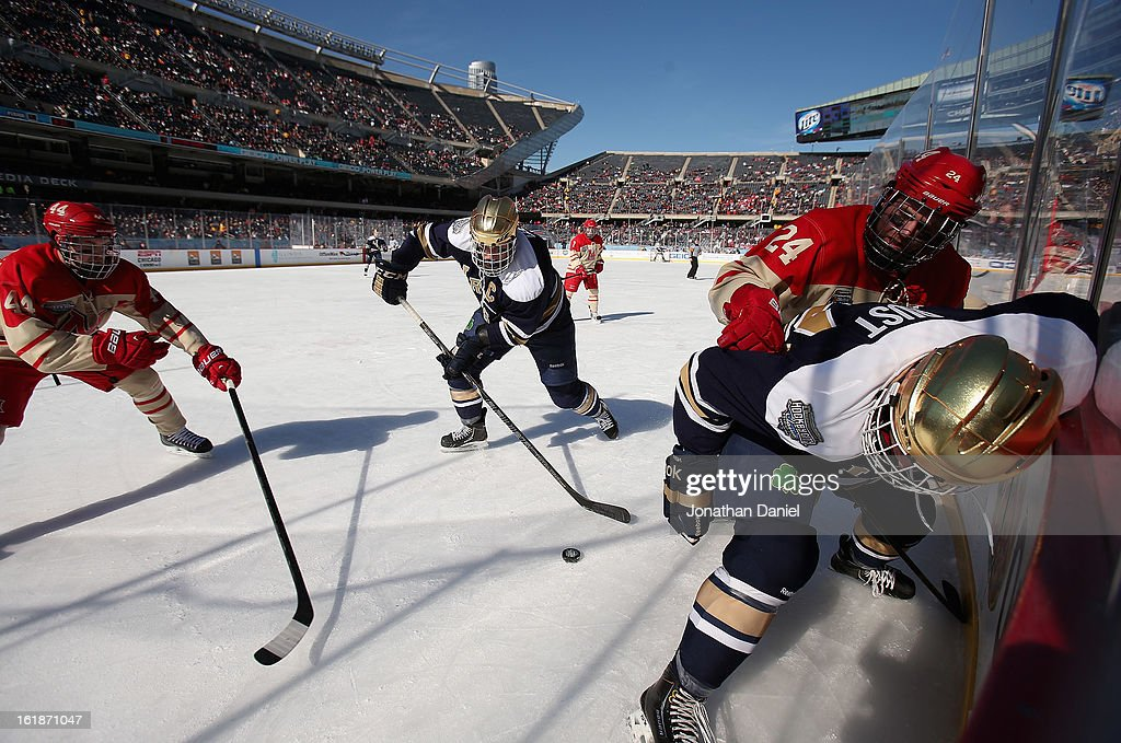 Anders Lee #9 of the Notre Dame Fighting Irish tries to clear the puck past teammate Bryan Rust #21 (L) and Steven Spinell #44 and Garrett Kennedy #24 of the Miami Redhawks during the Hockey City Classic at Soldier Field on February 17, 2013 in Chicago, Illinois.