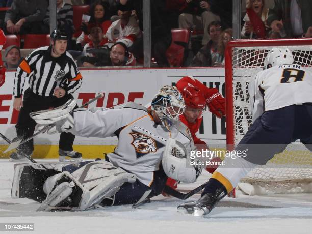 Anders Lindback of the Nashville Predators makes the save as Darren Helm of the Detroit Red Wings looks for the rebound at the Joe Louis Arena on...