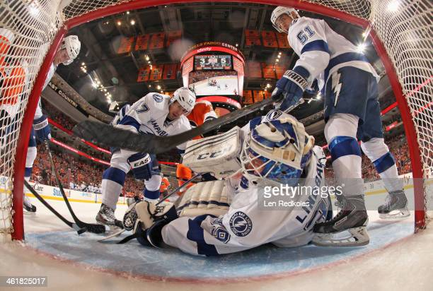 Anders Lindback of the Tampa Bay Lightning battles for the loose puck in his crease while teammates Andrej Sustr Alex Killorn and Valtteri Filppula...