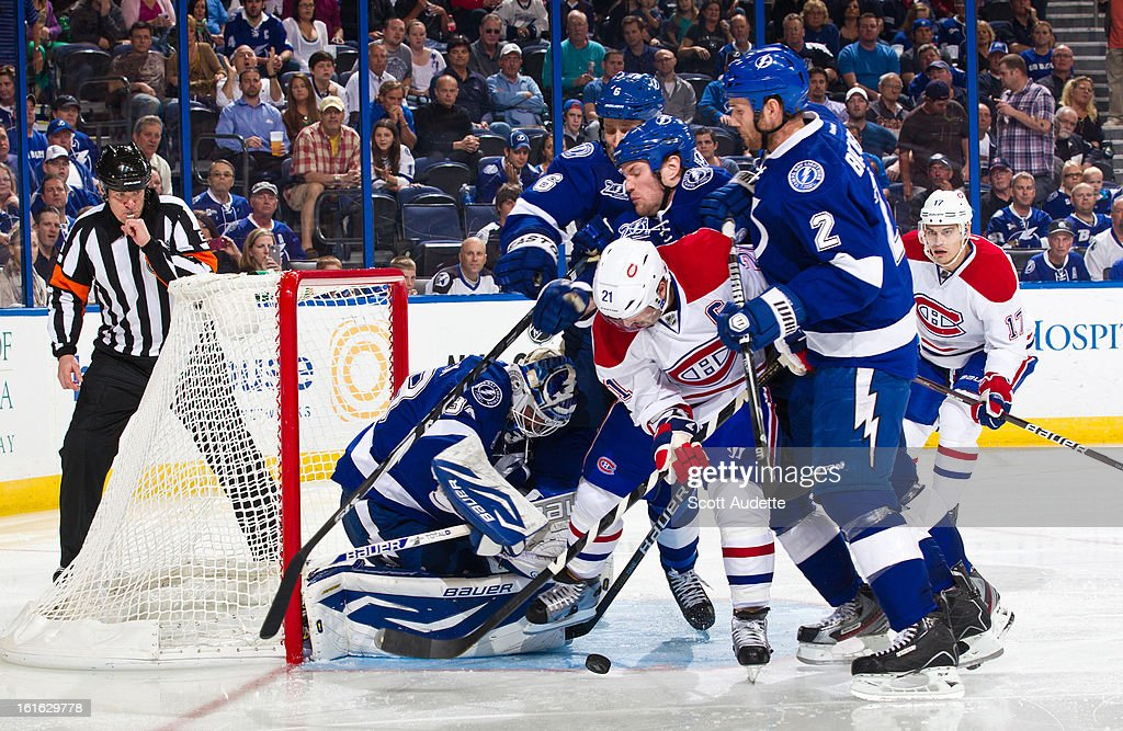 Anders Lindback #39 of the Tampa Bay Lightning blocks a shot as teammates Eric Brewer #2 and Sami Salo #6 pile up on Brian Gionta #21 of the Montreal Canadiens during the second period of the game at the Tampa Bay Times Forum on February 12, 2013 in Tampa, Florida.
