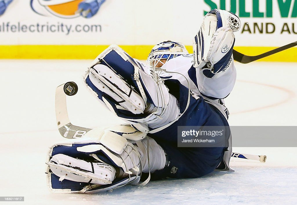 <a gi-track='captionPersonalityLinkClicked' href=/galleries/search?phrase=Anders+Lindback&family=editorial&specificpeople=7211274 ng-click='$event.stopPropagation()'>Anders Lindback</a> #39 of the Tampa Bay Lightning makes a save in the third period during the home opener game on October 3, 2013 at TD Garden in Boston, Massachusetts.