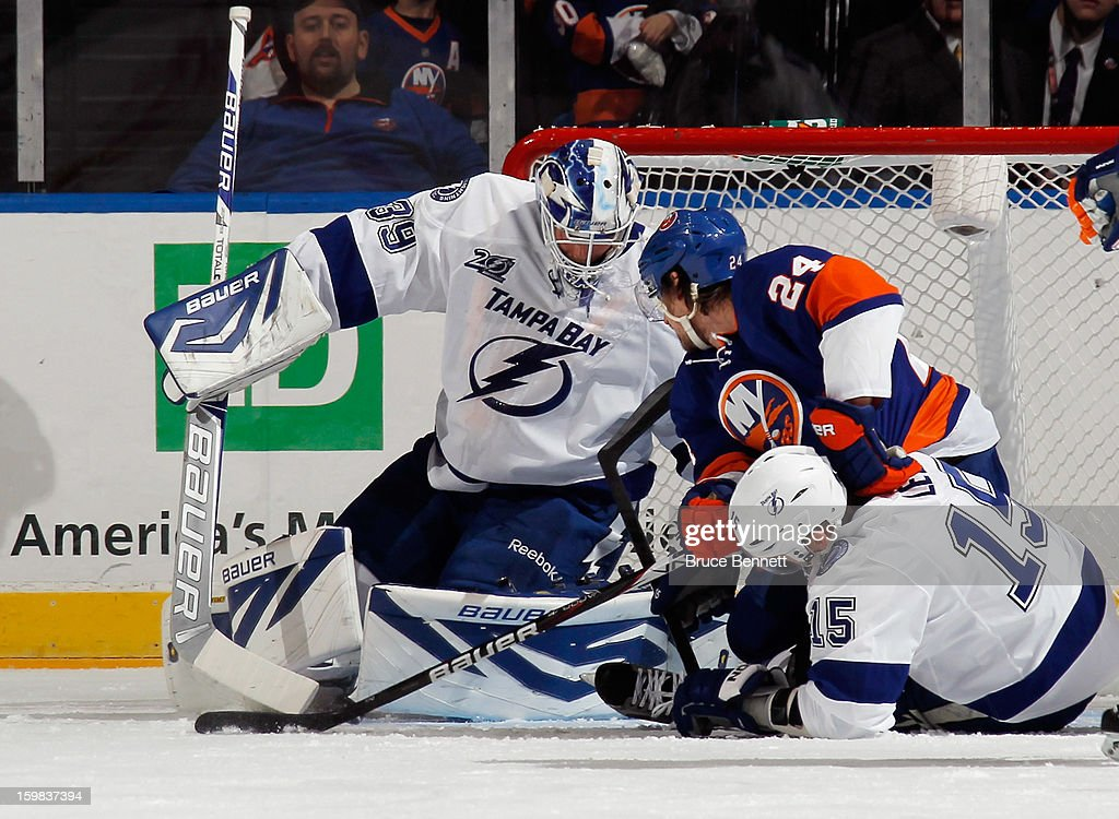 Anders Lindback #39 of the Tampa Bay Lightning makes the first period save as Brad Boyes #24 of the New York Islanders looks for the rebound at the Nassau Veterans Memorial Coliseum on January 21, 2013 in Uniondale, New York.