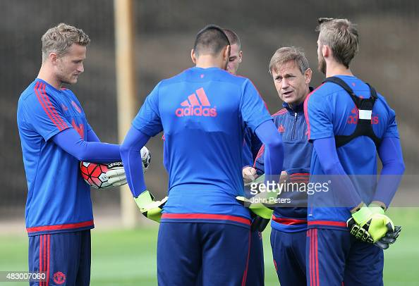 Anders Lindegaard Sergio Romero and David de Gea speak to Goalkeeping Coach Frans Hoek of Manchester United during a first team training session at...