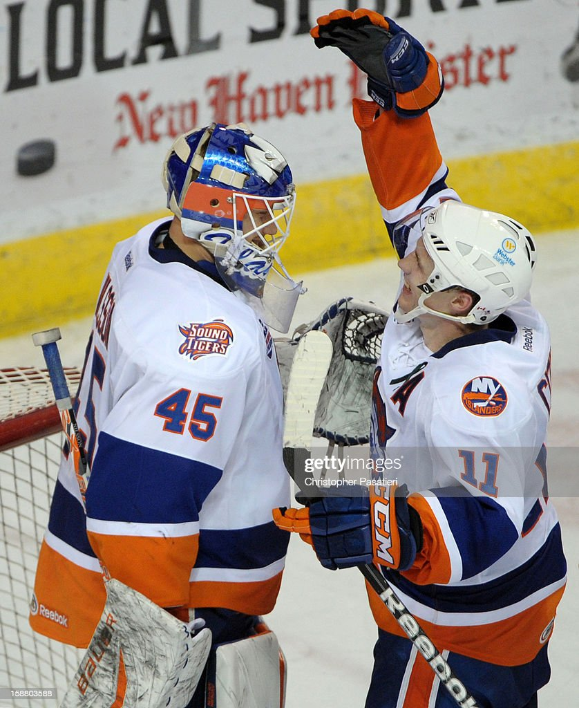 Anders Nilsson #45 of the Bridgeport Sound Tigers is congratulated by Casey Cizikas #11 after defeating the Manchester Monarchs during an American Hockey League game on December 29, 2012 at the Webster Bank Arena at Harbor Yard in Bridgeport, Connecticut.