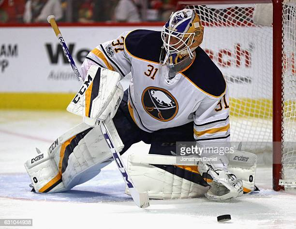 Anders Nilsson of the Buffalo Sabres knocks the puck away against the Chicago Blackhawks at the United Center on January 5 2017 in Chicago Illinois