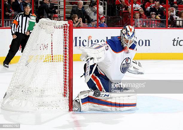 Anders Nilsson of the Edmonton Oilers deflects a puck away from the crease during a NHL game against the Carolina Hurricanes at PNC Arena on November...