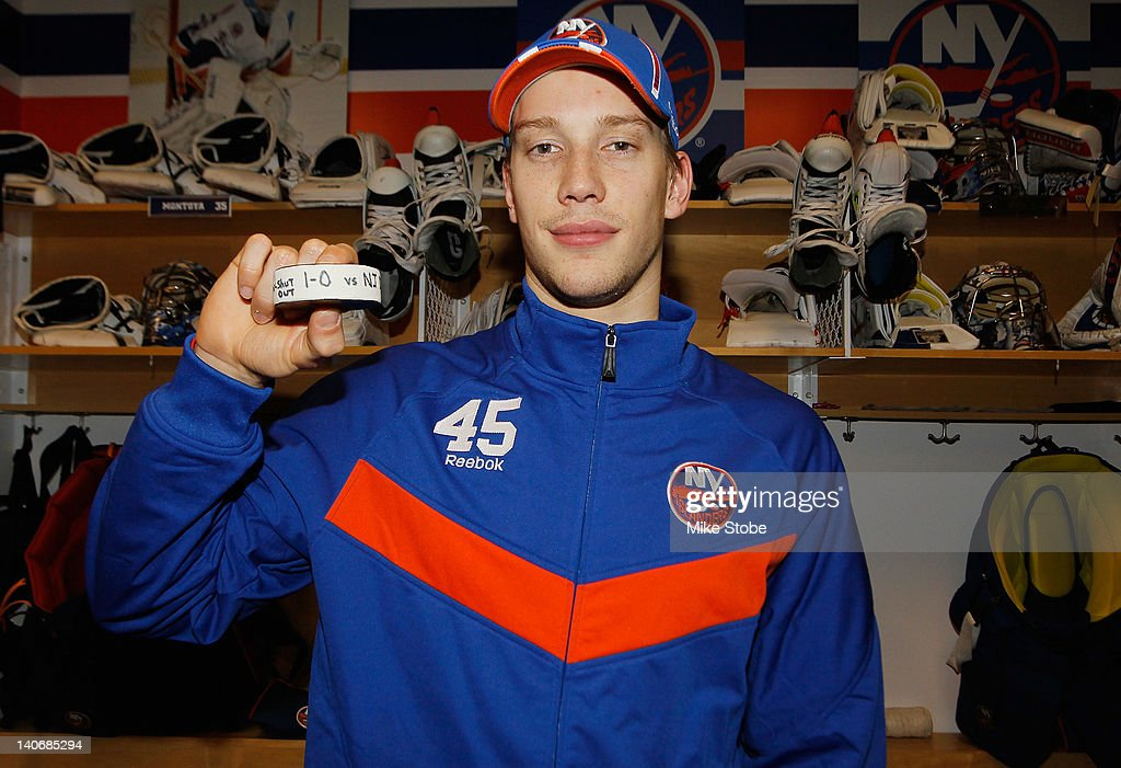 Anders Nilsson #45 of the New York Islanders poses with the game puck after defeating the New Jersey Devils for his first NHL victory and shutout at Nassau Veterans Memorial Coliseum on March 4, 2012 in Uniondale, New York. The Islanders defeat the Devils 1-0.