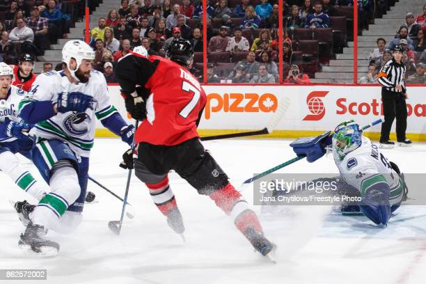 Anders Nilsson of the Vancouver Canucks makes a save against Kyle Turris of the Ottawa Senators as Erik Gudbranson of the Vancouver Canucks looks on...
