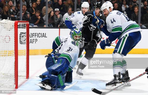 Anders Nilsson of the Vancouver Canucks makes the save against Dustin Brown of the Los Angeles Kings with help from Ben Hutton and Erik Gudbranson...