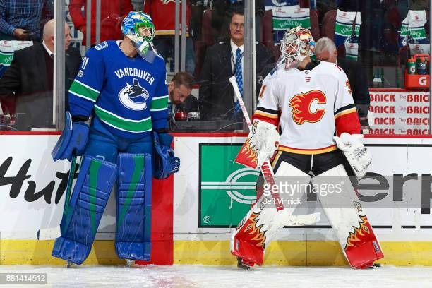 Anders Nilsson of the Vancouver Canucks talks with Eddie Lack of the Calgary Flames during warmup before their NHL game at Rogers Arena October 14...