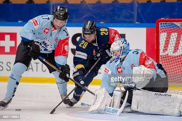 Anders Overmark of Sonderjyske tackles Chris Abbott of HV71 as Joni Myllykoski Goaltender of Sonderjyske covers the goal during the Champions Hockey...