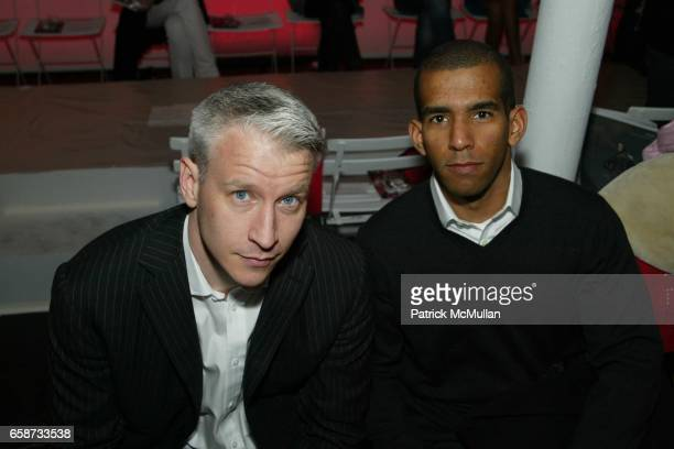 Anderson Cooper and Cesar Recio attend the front row at Diane von Furstenberg Fashion Show at DVF Studios on February 8 2004 in New York City