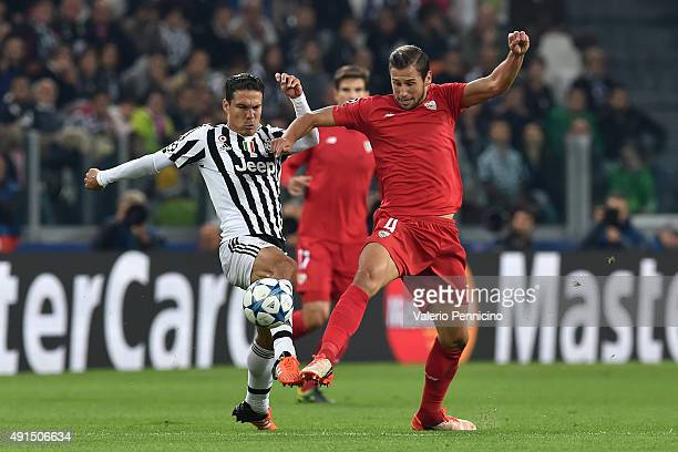 Anderson Hernanes of Juventus competes with Grzegorz Krychowiak of Sevilla during the UEFA Champions League group E match between Juventus and...