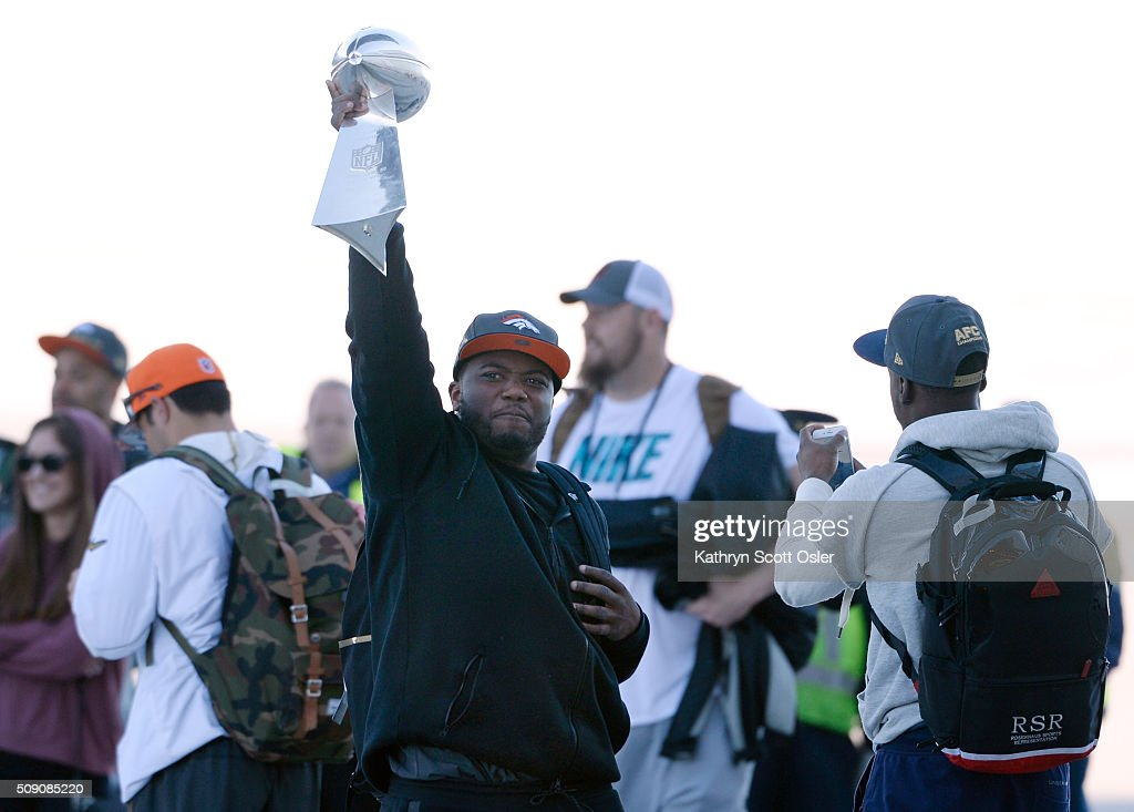 C.J. Anderson holds up the Vince Lombardi Tophy as he and members of the Denver Broncos football team arrive home at Denver international Airport on Monday, Feb. 8, 2016.