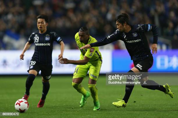 Anderson Lopes of Sanfrecce Hiroshima competes for the ball against Jin Izumisawa and Genta Miura of Gamba Osaka during the JLeague J1 match between...