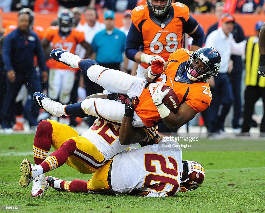 C. J. Anderson #22 of the Denver Broncos carries the ball against Josh Wilson #26 and Jordan Pugh #32 of the Washington Redskins at Sports Authority Field on October 27, 2013 in Denver, Colorado.