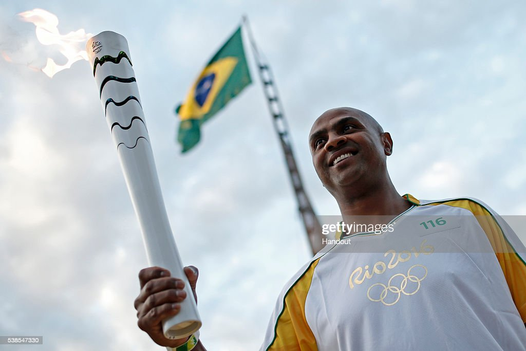 <a gi-track='captionPersonalityLinkClicked' href=/galleries/search?phrase=Anderson+Oliveira&family=editorial&specificpeople=2360303 ng-click='$event.stopPropagation()'>Anderson Oliveira</a> holds the olympic torch during day 12 of the Olympic Flame torch relay on May 14 , 2016 in Brasilia, Brazil. The Olympic torch will pass through 329 cities from all states from the north to the south of Brazil, until arriving in Rio de Janeiro on August 5, to lit the cauldron.