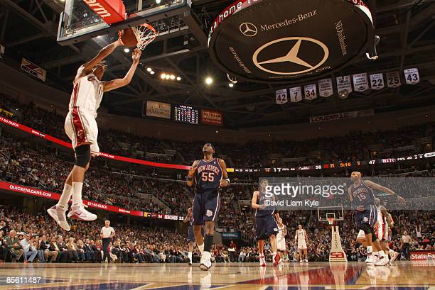 Anderson Varejao of the Cleveland Cavaliers dunks on a fast break trailed by Keyon Dooling Brook Lopez and Vince Carter of the New Jersey Nets at The...