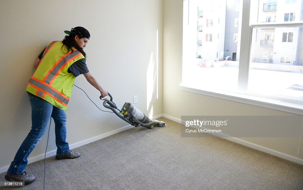 andi escarcida vacuums a bedroom of an apartment as workers are doing
