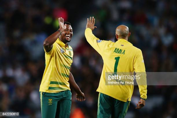 Andile Phehlukwayo of South Africa celebrates with teammate Hashim Amla for the wicket of Kane Williamson of New Zealand during the first...