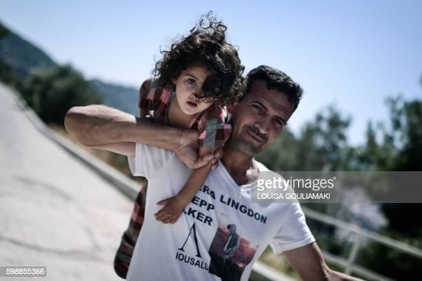 TOPSHOT Ando Elias Tareq 36 a Yezidi from Sinjar in Iraq holds his yougest daughter outside the Samos hotspot where they live on September 1 2016...