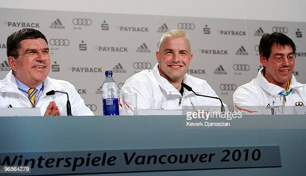 André Lange reacts as Dr Thomas Bach a vicepresident and member of the executive board of the International Olympic Committee and Bernhard Schwank...