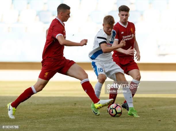 Andras Schafer of MTK Budapest II dribbles between Corey Whelan of FC Liverpool U23 and Lloyd Jones of FC Liverpool U23 during the Preseason Friendly...