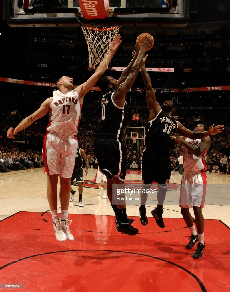 Andray Blatche #0 and Reggie Evans #30 of the Brooklyn Nets go up for a rebound against Jonas Valanciunas #17 of the Toronto Raptors on December 12, 2012 at the Air Canada Centre in Toronto, Ontario, Canada.