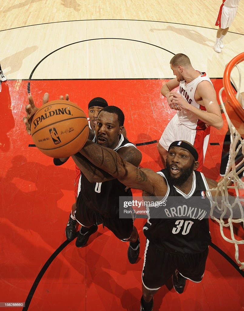 Andray Blatche #0 and Reggie Evans #30 of the Brooklyn Nets go up for a rebound against the Toronto Raptors on December 12, 2012 at the Air Canada Centre in Toronto, Ontario, Canada.