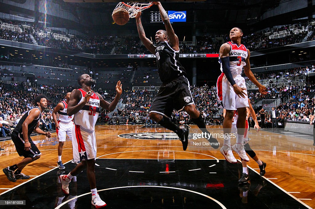 <a gi-track='captionPersonalityLinkClicked' href=/galleries/search?phrase=Andray+Blatche&family=editorial&specificpeople=4282797 ng-click='$event.stopPropagation()'>Andray Blatche</a> #0 of the Brooklyn Nets dunks against <a gi-track='captionPersonalityLinkClicked' href=/galleries/search?phrase=Bradley+Beal&family=editorial&specificpeople=7640439 ng-click='$event.stopPropagation()'>Bradley Beal</a> #3 of the Washington Wizards at the Barclays Center on October 15, 2012 in the Brooklyn borough of New York City.