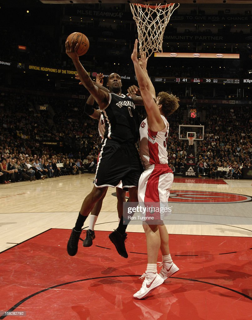 Andray Blatche #0 of the Brooklyn Nets goes to the basket against Aaron Gray #34 of the Toronto Raptors December 12, 2012 at the Air Canada Centre in Toronto, Ontario, Canada.
