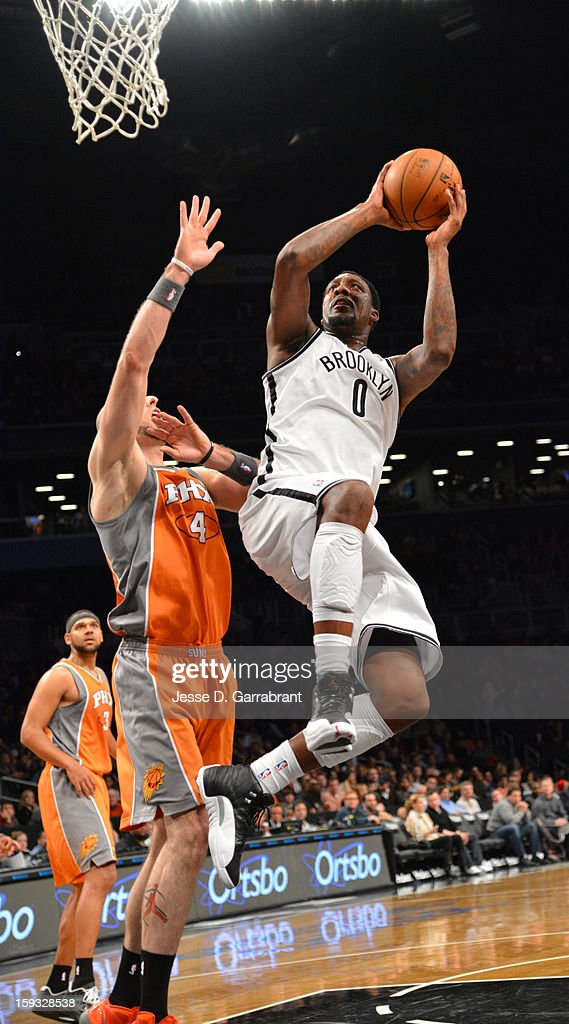 Andray Blatche #0 of the Brooklyn Nets shoots against Marcin Gortat #4 of the Phoenix Suns during the game at the Barclays Center on January 11, 2013 in Brooklyn, New York.