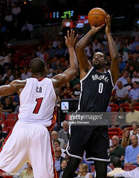 Andray Blatche of the Brooklyn Nets shoots over Chris Bosh of the Miami Heat during a game at American Airlines Arena on March 12 2014 in Miami...