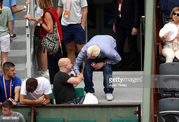 Andre Agassi coach of Novak Djokovic speaks with Boris Becker on day two of the 2017 French Open at Roland Garros on May 29 2017 in Paris France