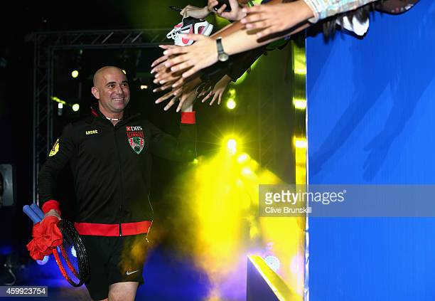 Andre Agassi of the Singapore Slammers high fives the fans as he runs out for his teams match against the UAE Royals during the CocaCola...