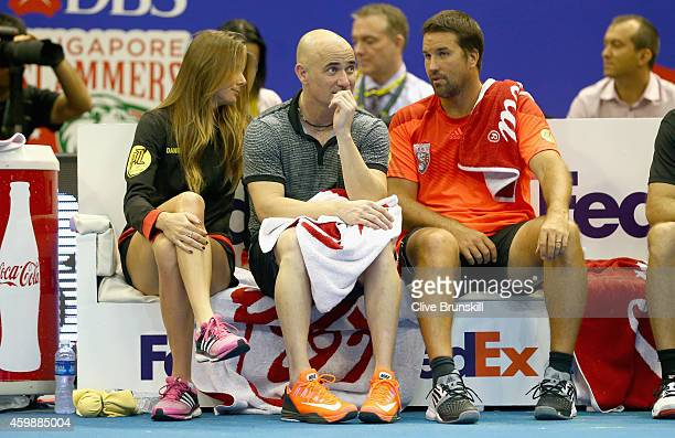 Andre Agassi Patrick Rafter and Daniela Hantchova of the Singapore Slammers sit on the team bench during their match against the Indian Aces during...