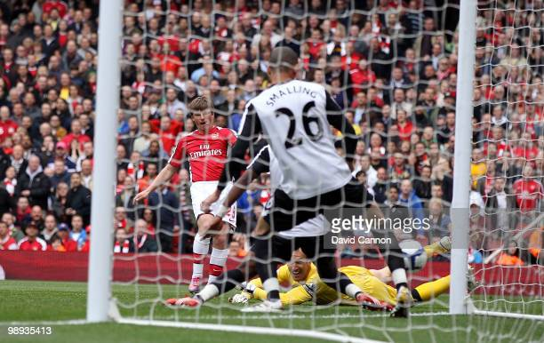 Andre Arshavin of Arsenal threads the ball past Mark Schwarzer of Fulham and Chris Smalling of Fulham to score Arsenal's first goal during the...