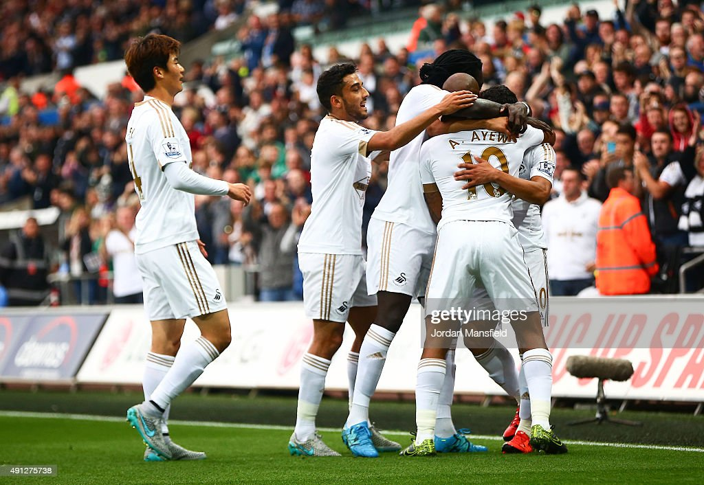 Andre Ayew of Swansea City celebrates scoring Swansea's first goal with team mates during the Barclays Premier League match between Swansea City and Tottenham Hotspur at Liberty Stadium on October 4, 2015 in Swansea, Wales.