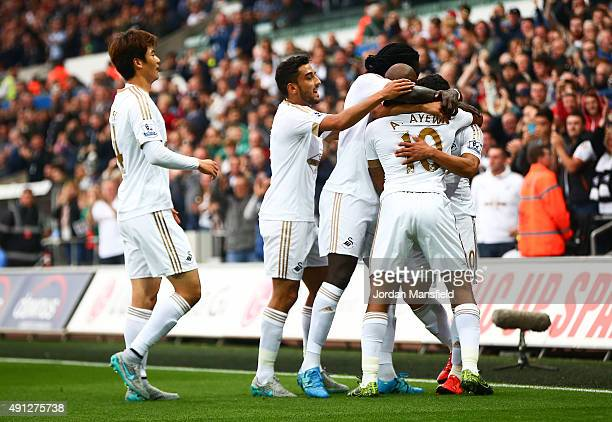 Andre Ayew of Swansea City celebrates scoring Swansea's first goal with team mates during the Barclays Premier League match between Swansea City and...