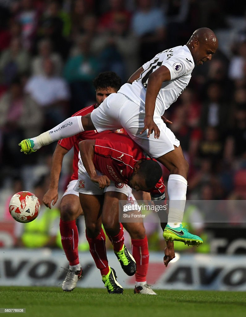 Andre Ayew of Swansea City is challenged by Nathan Thompson of Swindon during the Pre Season friendly between Swindon Town and Swansea City at County...