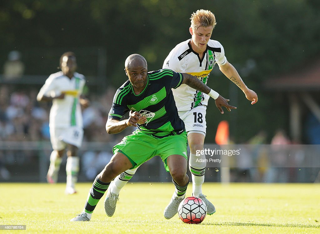 Andre Ayew of Swansea is challenged by Marvin Schulz of Borussia Moenchengladbach during the City Preseason Friendly between Borussia Moenchengladbach and Swansea at Grassau on July 15, 2015 in Grassau, Germany.