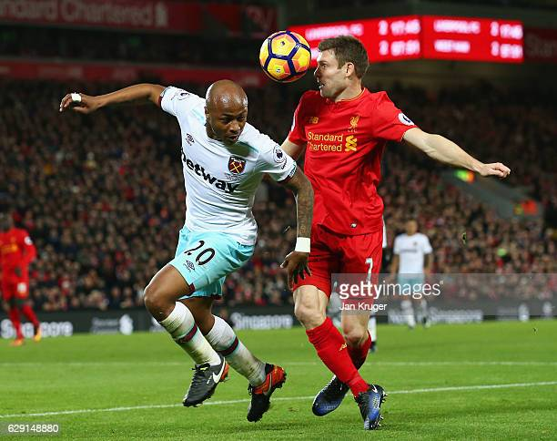 Andre Ayew of West Ham United and James Milner of Liverpool compete for the ball during the Premier League match between Liverpool and West Ham...